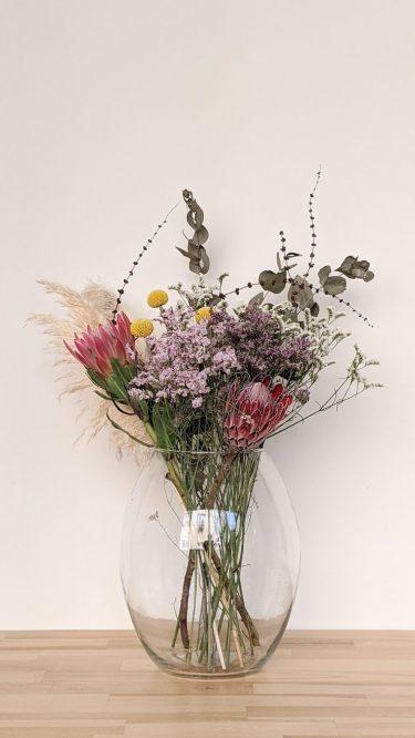 היוניקה השמחה הזו מכילה פרחים מיובשים הכוללים פרוטיאה, חרדלית, קרספידיה, אקליפטוס, לימוניום בשלל צבעים ופמפס בכלי זכוכית אובלי יפהפה.