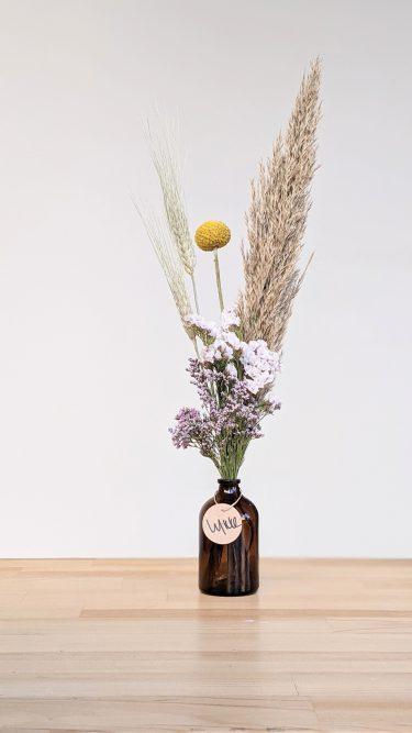 הליקה הזו מכילה פרחים מיובשים של פמפס, קרספידיה ופרחים בצבעוניות עדינה (לימוניום ו/או גיבסנית ו/או עדעד) כמו גם חיטה בתוך בקבוקון זכוכית חום