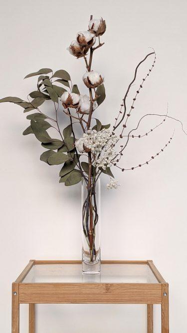 היוניקה הזו מכילה כותנה, אקליפטוס וחרדלית מיובשים, פרחים בצבעים נייטרליים (גיבסנית ולימוניום סינסי), וערבה מסולסלת בכלי צילנדר זכוכית שקוף