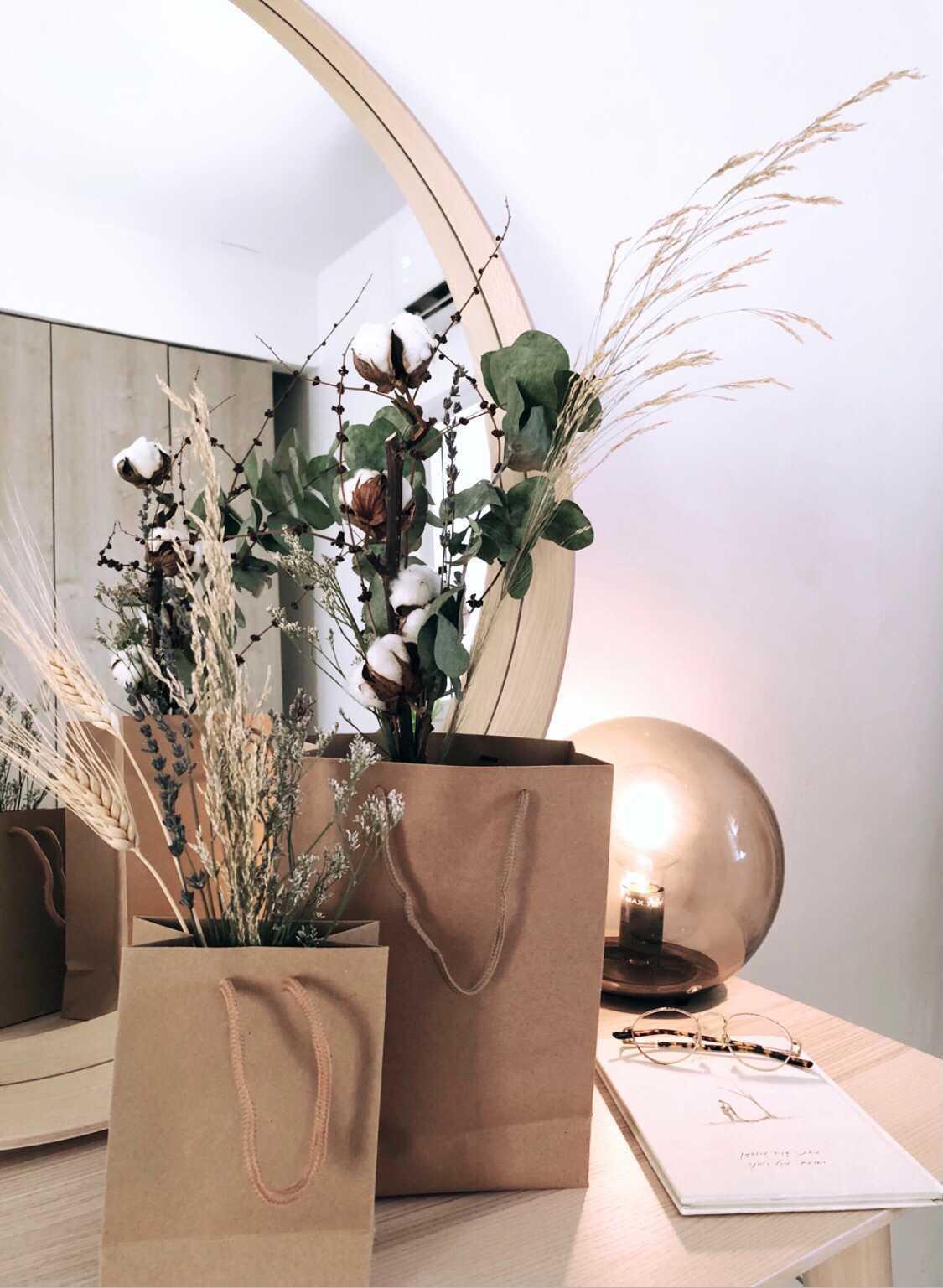 סידורי פרחים מיובשים כותנה פמפס אקליפטוס חיטה לבנדר יבשים בשקיות חומות של ליקות על שולחן חדר שינה מעוצב
