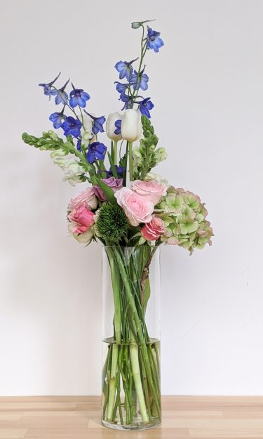ואזה כלי שקוף עם פרחים טריים של הורטנזיה לילי טוליפ וורדים