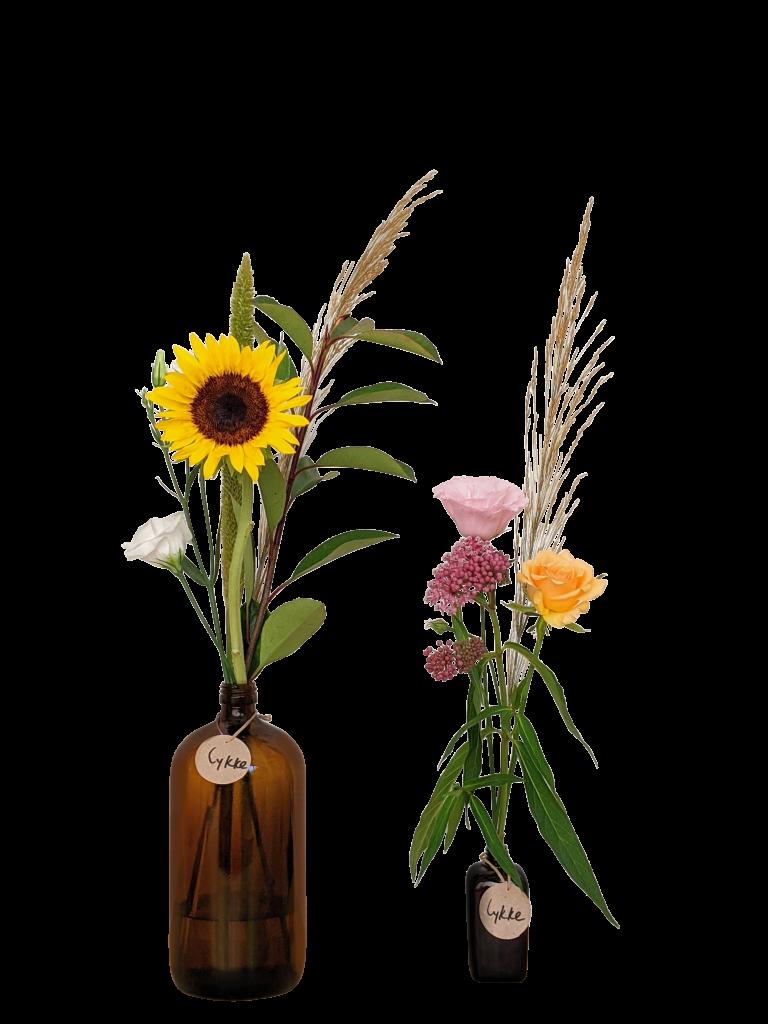 מיני בקבוק חום בסגנון יפני עם סידור פרחים טריים צבעוניים בשילוב פרחים יבשים לצד בקבוק מקסי חום עם פרח חמניה ופרחים ירוקים